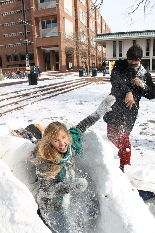 """Grad student, Asadullah Naweed throws snowballs at sophomores Cyara De Lannoy and Cassy Karlsson. """"You can't hit us, we have a fort for protection!"""" Karlsson said.  The girls had been taking shifts guarding their fort all day, because people had been trying to take it."""
