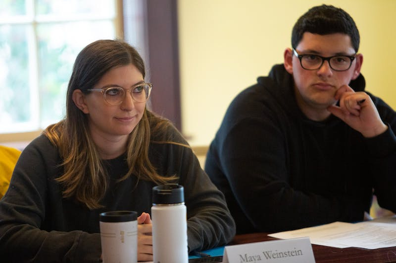 """Law student Maya Weinstein (left) and student Joshua Romero, members of the Campus Safety Commission, listen to remarks during a meeting in Carroll Hall on Wednesday, Jan. 15, 2020, ahead of the Summit of Safety and Belonging. """"I really feel like they created this mostly, and it's not us giving feedback and listening more and putting the Chancellor in the hot seat,"""" Weinstein said. """"It does feel more of like a presentation and parade of all these things. And I will accept that for this because we have two weeks."""""""
