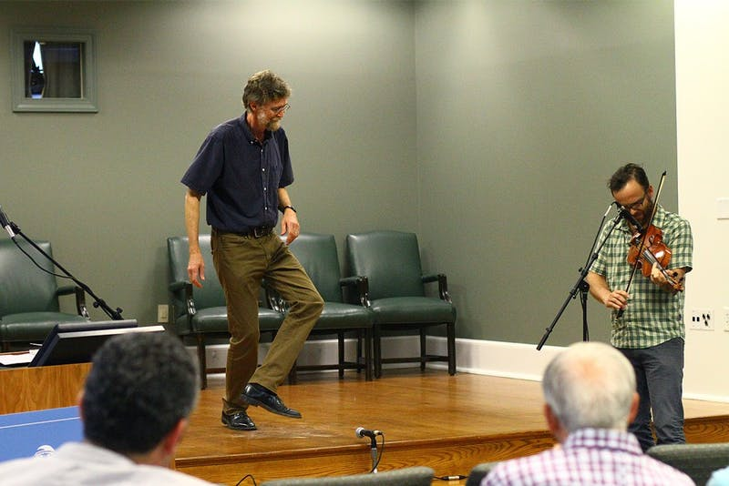"""Phil Jameson, a professor at Warren Wilson College, performs in front of an audience in Wilson Library. He recently published the book """"Hoedowns, Reels, and Frolics: Roots and Branches of Southern Appalachian Dance."""""""