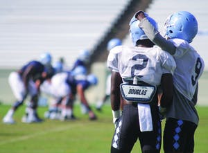 UNC football players watch their teammates from the sideline during team practice on Aug. 21.