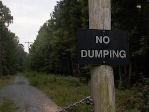 """A """"No Dumping"""" sign is pictured on The Greene Tract in Chapel Hill, NC. The Green Tract is a parcel of land owned by Orange County, Chapel Hill, and Carrboro."""