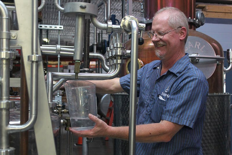 George Dusek is the head distiller at TOPO's distillery, located on the corner of West Franklin and South Graham streets. Distilleries are not allowed to sell liquor after tours under the current system. TOPO owner Scott Maitland drafted a bill to allow this after popular demand.