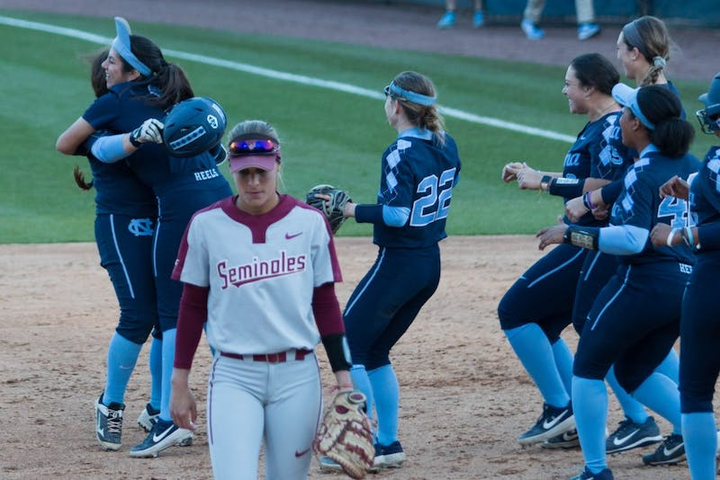 FSU senior infield Carsyn Gordon (12) leaves the field as UNC players celebrate their victory after a double header G. Anderson Softball Stadium on Monday, April 15, 2019. The Tar Heels beat the Seminoles in both games.