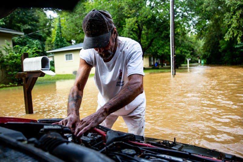 James Allen checks the engine of his car while standing in flood waters. It was left running when the street flooded. There was a loud boom and white smoke began to radiate from under the hood. As soon as the water had receded low enough, Allen went to check the damage.