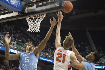 (From left) UNC first-year forward Armando Bacot (5), Syracuse junior forward Marek Dolezaj (21) and UNC junior forward Garrison Brooks (15) fight to gain possession of the ball in the second round of the 2020 New York Life ACC Tournament held in the Greensboro Coliseum in Greensboro, N.C., on Wednesday, March 11, 2020. UNC lost 81-53.