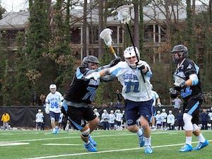 Junior defenseman Zach Powers (77) carries the ball down the field.