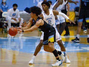 UNC first year guard Caleb Love (2) attempts to block a pass by Marquette sophomore guard D.J. Carton (21) during a game in the Smith Center on Wednesday, Feb. 24, 2021. UNC lost to Marquette 83-70.