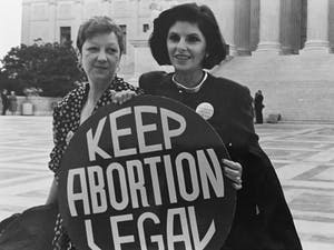 Norma McCorvey (left), the plaintiff of Roe v. Wade, died at age 69. Here, McCorvey (Jane Roe) and her lawyer Gloria Allfred stand on the steps of the Supreme Court, 1989. Photo courtesy of Lorie Shaull.