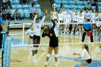 Sophomore opposite and outside hitter Destiny Cox (1) and junior middle blocker Aristea Tontai (3) team up for a block attempt against Miami's Janet Kalaniuvalu (6) on Friday, Oct. 11, 2019 in Carmichael Arena. UNC beat Miami 3-1.