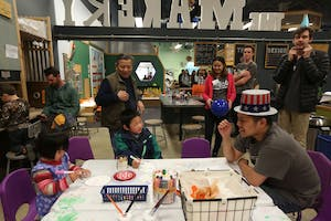 Kids do a coloring activity in celebration of Kidzu's 11th birthday as parents and counselors look on at University Mall on Sunday.