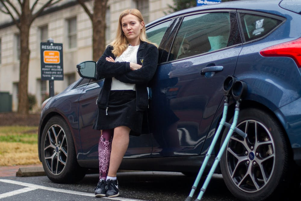"""Erin Day, a graduate student in UNC's chemistry department, stands in front of her car in a disabled parking lot near Caudill Labs on Tuesday, Jan. 26, 2021. """"It's such a complicated path,"""" says Day of her struggle to obtain a disabled parking permit. """"It feels like the university at large doesn't want you to get it."""""""