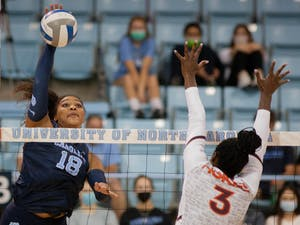 Graduate outside hitter Nia Robinson (18) spikes the ball in the UNC Women's volleyball game against Virginia Tech at the Woolen Gymnasium on Oct. 10. The Heels won 3-0.