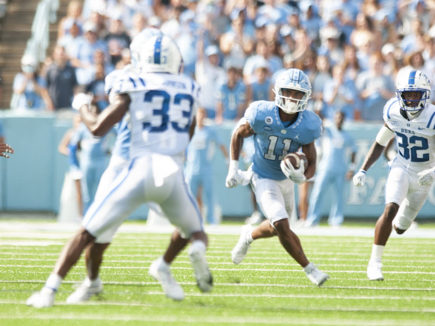 Sophomore wide receiver Josh Downs (11) receives a 63-yard pass from quarterback Sam Howell (7) and runs up the field to score a touchdown, bringing the Tar Heels to a 38-7 lead over Duke. The Tar Heels defeated Duke 38-7 in Kenan Memorial Stadium on Oct. 2, 2021.