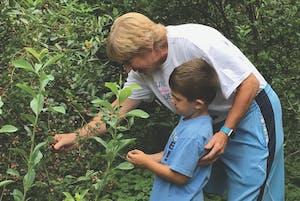 UNC women's basketball coach Sylvia Hatchell picks blueberries with her godson, Luke Marlowe.