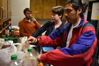 (From left to right) Hinton James RA's Andrew Robinson, Laura Wilders and Alex Ramirez help themselves to leftover food and drinks in the office after a community event on Tuesday, Nov. 13, 2018.