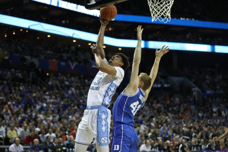 Duke junior forward Jack White (41) attempts to block a shot by UNC graduate guard Cameron Johnson (13) in the semifinals of the ACC Tournament at the Spectrum Center in Charlotte, N.C. on Friday, March 15, 2019. UNC fell to Duke 73-74.