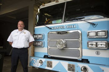 Chief Sullivan poses next to one of the well-known blue fire trucks at the Chapel Hill Fire Department on Friday, Oct. 4, 2019.