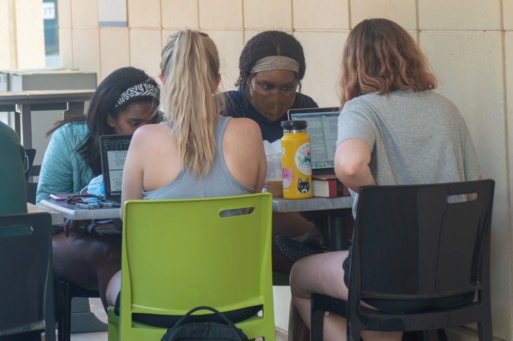 <p>A group of students work on school work together outside of the student union on Tuesday, Apr. 27, 2021.</p>