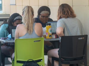 A group of students work on school work together outside of the student union on Tuesday, Apr. 27, 2021.