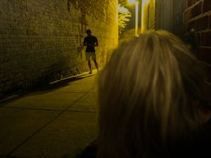 DTH Photo Illustration. A woman sits in an alley, alone, while a man on his phone walks by paying no attention to her.