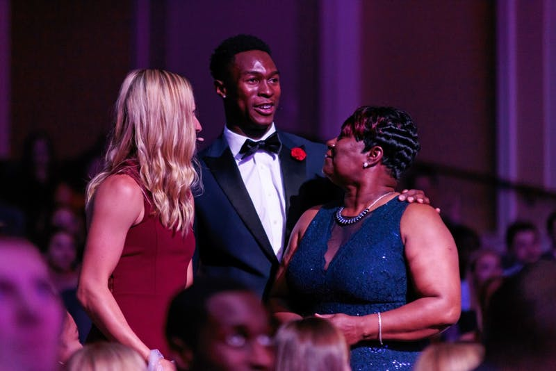 Emcees Marika Akkerman (women's tennis) and Kenny Selmon (track and field) present Gwen Warren with the Unsung Hero Award at the Rammys on April 23 in Memorial Hall.