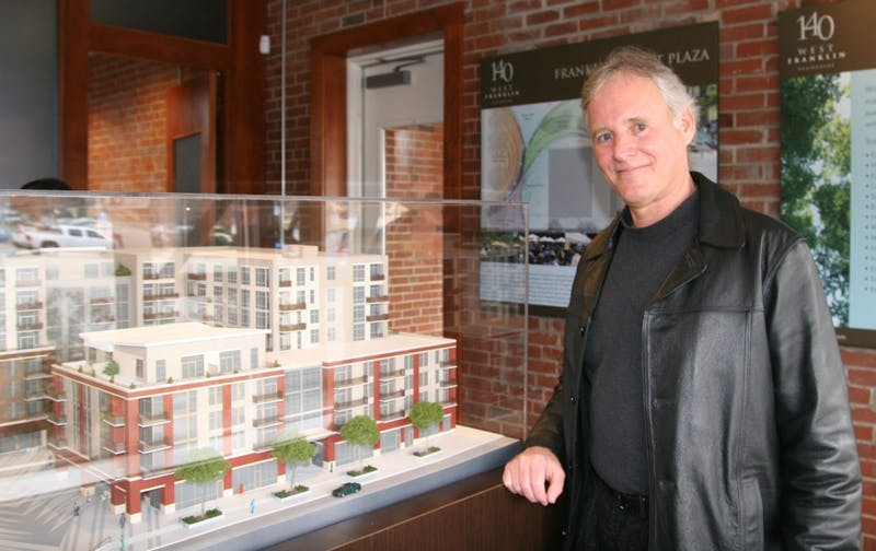 Bill Spiegel, a Chatham County resident and new 140 West Franklin homeowner, stands in front of a showroom model of the development. Spiegel said he values the downtown location of the complex.