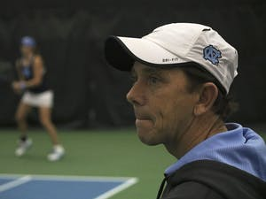 North Carolina women's tennis head coach Brian Kalbas watches as his team beats Texas A&M 4-0.