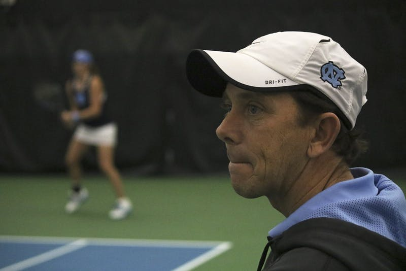 North Carolina women's tennis head coach Brian Kalbas watches as his team beats Texas A&M 4-0.