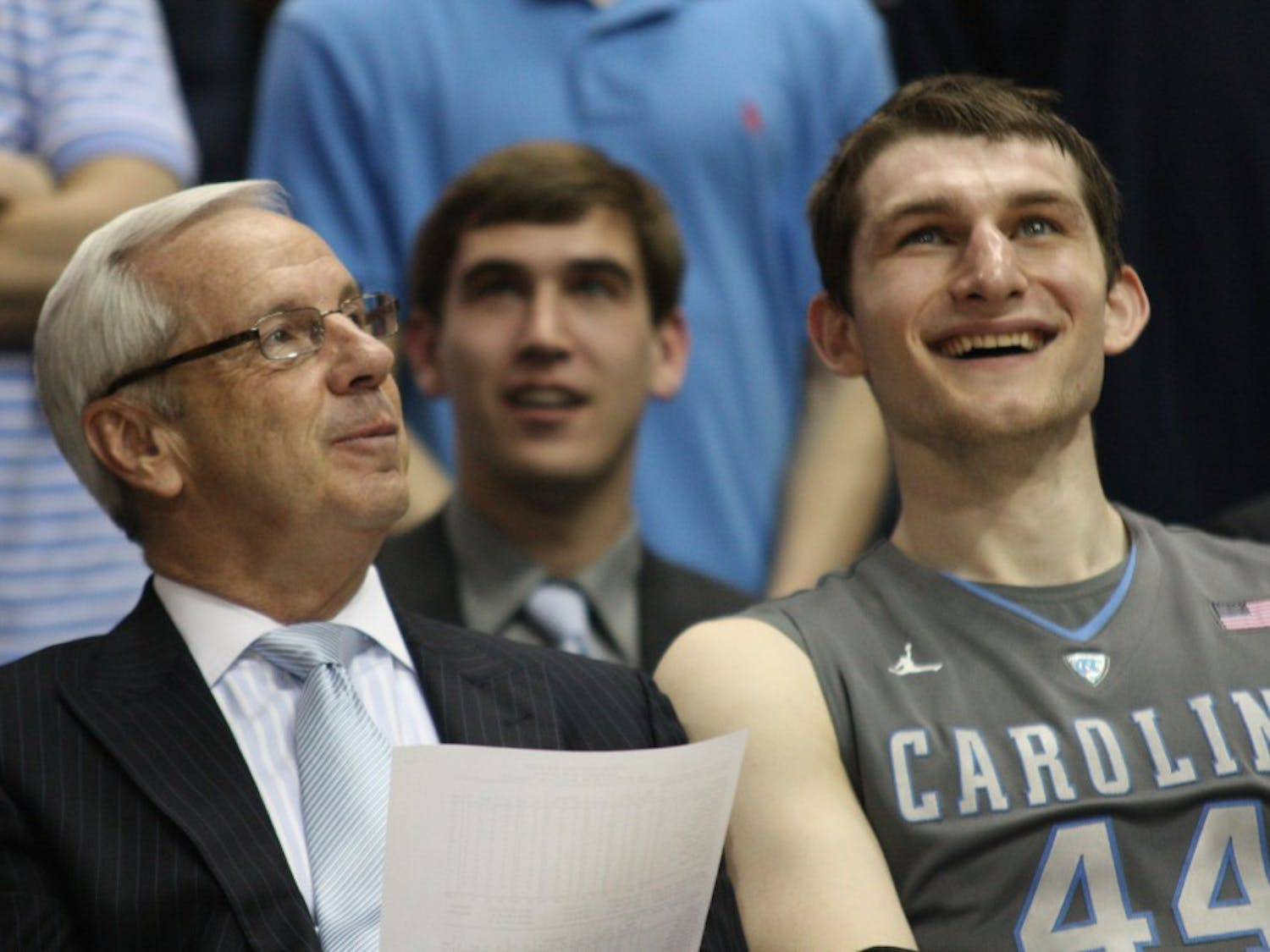 Coach Roy Williams and Tyler Zeller laugh while watching the senior video after the game