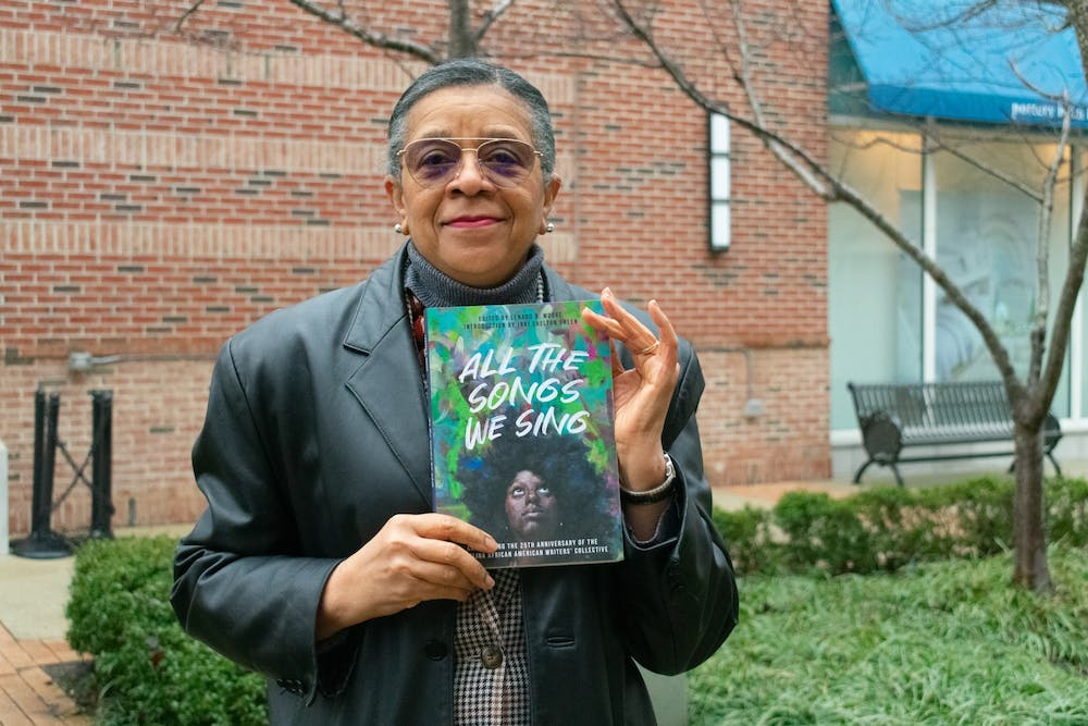 "The Carolina African American Writers' Collective was founded in 1995; four members of the group read from the newly released anthology ""All The Songs We Sing"" on Tuesday, February 9th, 2021. Here, L. Teresa Church stands with a copy of the anthology."