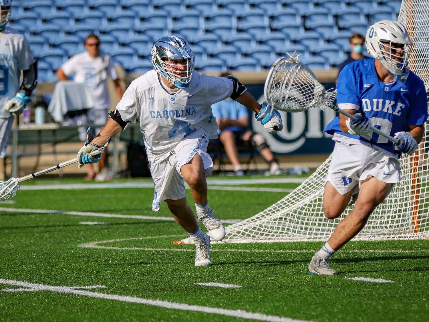 UNC senior attackman Chris Gray (4) attempts to regain possession from Duke graduate goalkeeper Mike Adler (0) during the Tar Heels' 15-12 victory against Duke on Sunday, May 2. With the victory, UNC and Duke share the 2021 ACC regular season title.