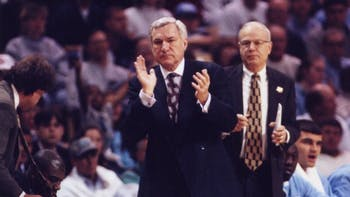 Former North Carolina men's basketball head coach Dean Smith (left) and Bill Guthridge, his top assistant, in 1997. A young Vasco Evtimov sits to Guthridge's right. DTH file photo.