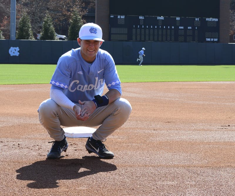 Former UNC shortstop Logan Warmoth grabs some clay in front of the scoreboard at Boshamer Stadium in Chapel Hill.