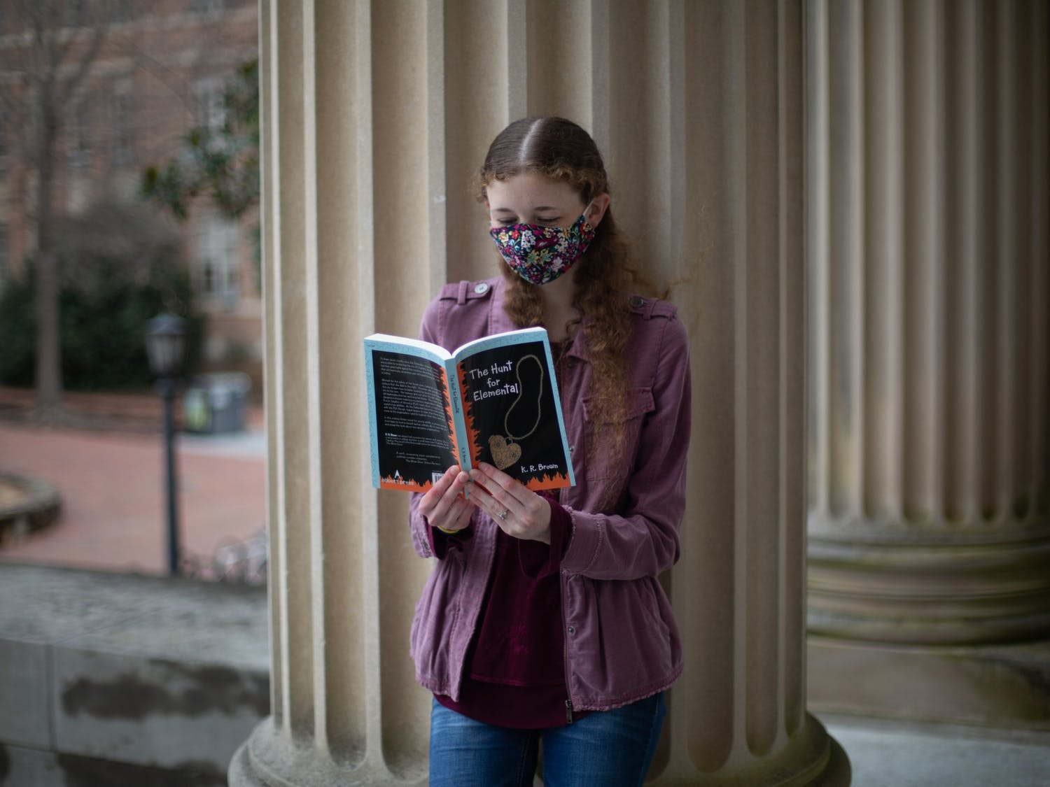 Senior communications major and author Kristen Brown poses for a portrait with her latest book, The Hunt for Elemental, in front of Wilson Library on Saturday, Feb. 27, 2021. Brown has plans for at least nine books in the series but hopes there will be more.
