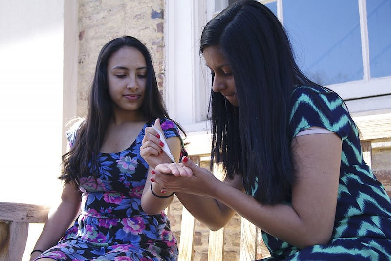 Sophomore psychology major Alopi Modi (right) applies henna on freshman public health major Simran Khadka Wednesday afternoon.