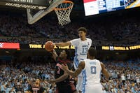 Louisville sophomore guard Darius Perry (2) attempts a layup against UNC guards Cameron Johnson (13) and Seventh Woods (0) during the Tar Heels' 83-62 loss against Louisville on Saturday, Jan. 12, 2019 in the Smith Center.