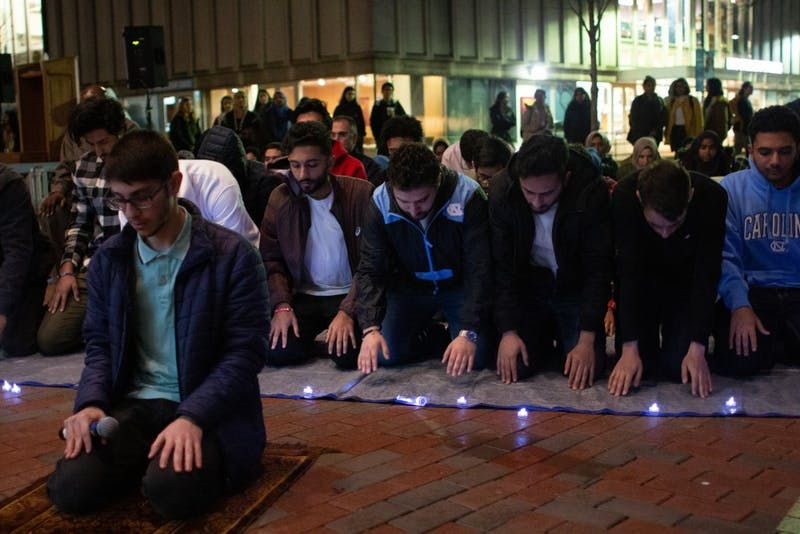 Students and community members join each other in a prayer led by sophomore computer science major and mathematics minor Omar Shaban (left) following a vigil hosted by the Muslim Student Association outside of the Student Union on Thursday, March 21, 2019. The event honored the victims of the Christchurch shooting in New Zealand, during which a shooter claimed the lives of 51 people during Friday Prayer.