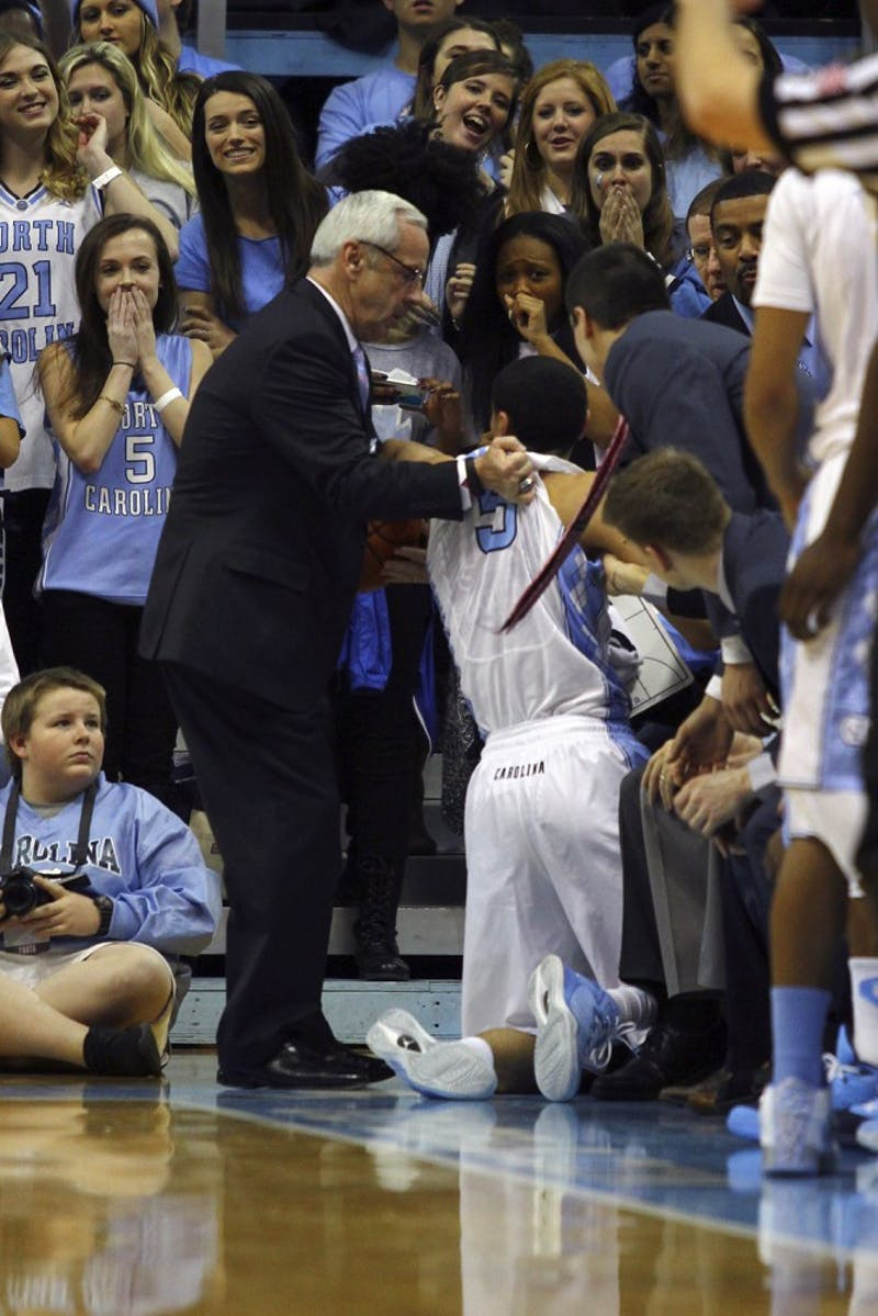 UNC head coach Roy Williams picks junior guard Marcus Paige (5) up after he fell out of bounds.