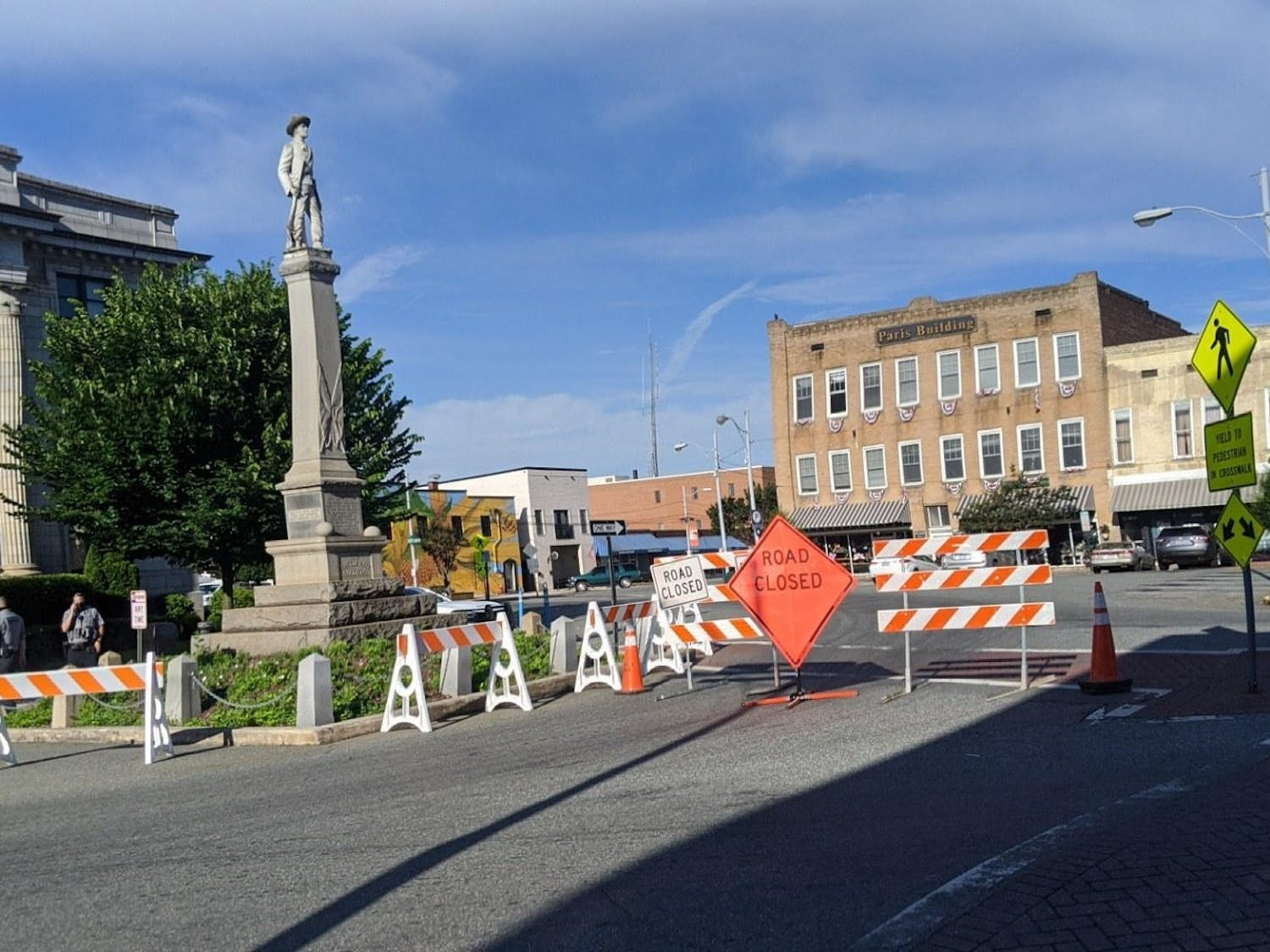 The Alamance County Confederate Monument in Graham, NC is surrounded by road barricades and signs. Photo courtesy of Colin Dodd.