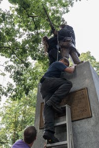 Protesters climb Silent Sam to cover the statue with a black flag during Sunday's vigil.