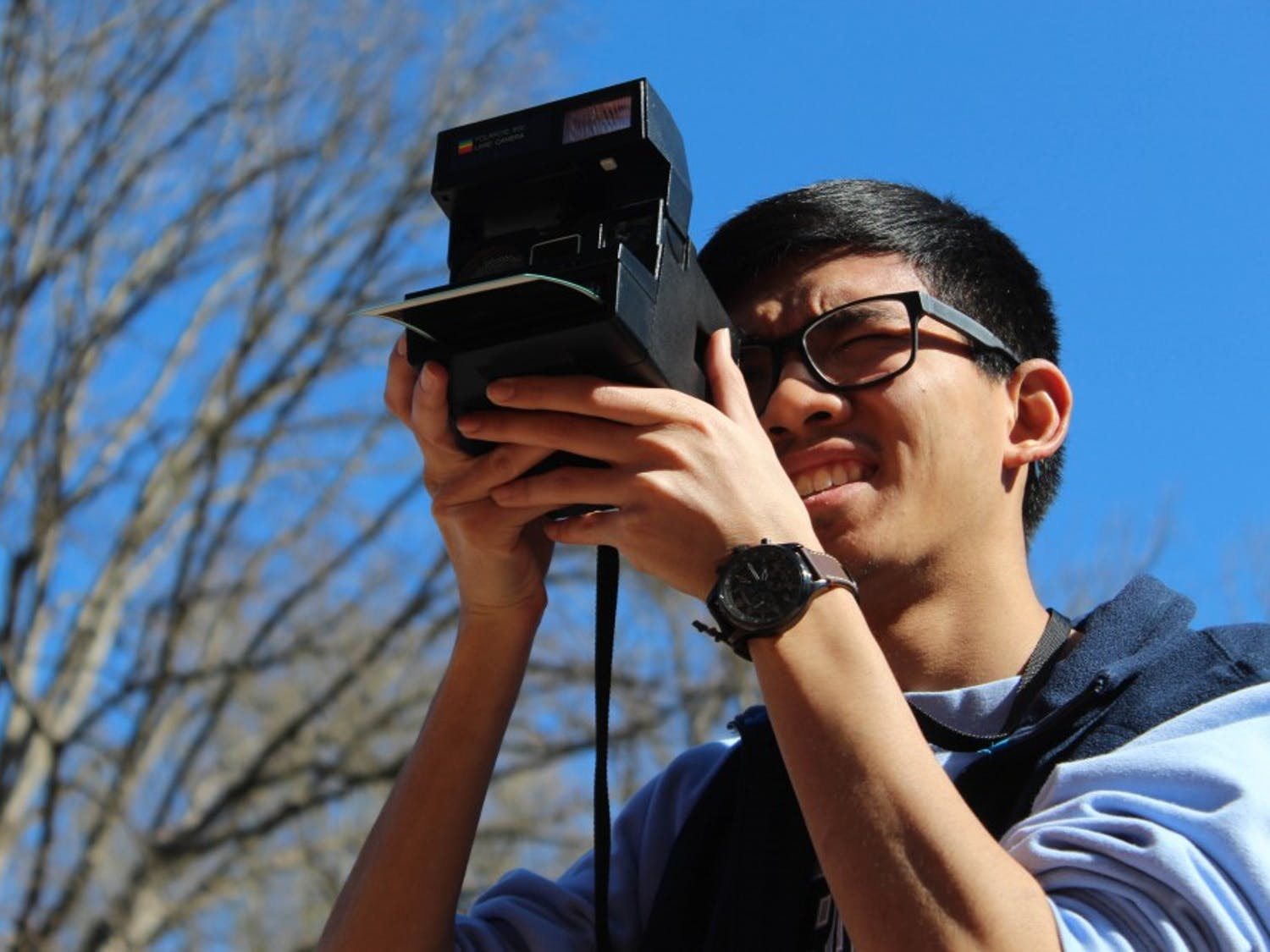 """Lucky Prachith, senior business major, uses his Polaroid camera at South Building on Tuesday, March 26, 2019. Prachith likes taking photos with his Polaroid camera because """"it's a medium that's different in the sense that at the end of the day you get a tangible thing, it has a realness that separates it from digital photography."""" Pracith has been shooting with his Polaroid since his senior year of high school."""