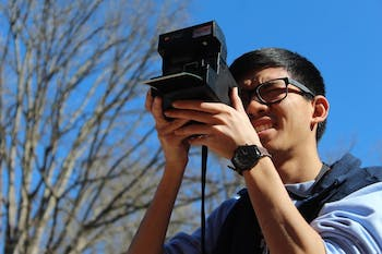 "Lucky Prachith, senior business major, uses his Polaroid camera at South Building on Tuesday, March 26, 2019. Prachith likes taking photos with his Polaroid camera because ""it's a medium that's different in the sense that at the end of the day you get a tangible thing, it has a realness that separates it from digital photography."" Pracith has been shooting with his Polaroid since his senior year of high school."