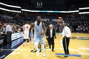 Forward Theo Pinson (1) and head coach Roy Williams leave the court after UNC's 85-75 win over Davidson in the Spectrum Center in Charlotte.