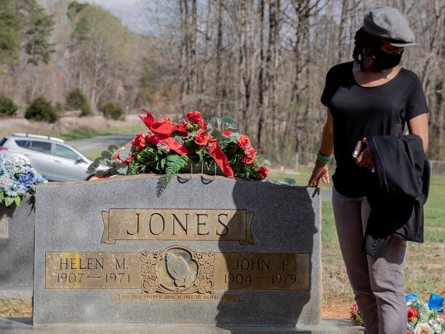 Shontea Smith, executive director of United Voices of Efland-Cheeks, stands next to a grave in her family's plot in Cheeks Crossing, North Carolina. Smith wrote a letter detailing the impact that development has had on the Cheeks community, and why the current development plans are harmful to her community.