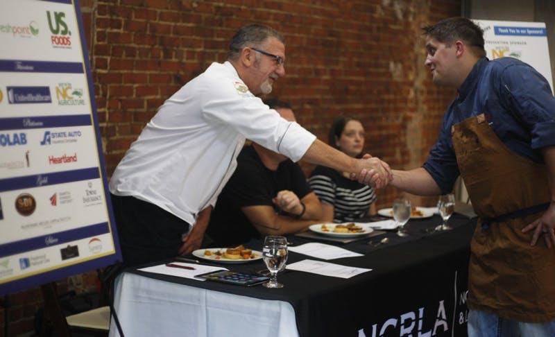 Executive chef of 21C Counting House, Thomas Card, shakes hands with one of the judges before his presentation during the 2019 NCRLA Chef Showdown on Monday July 22, 2019.