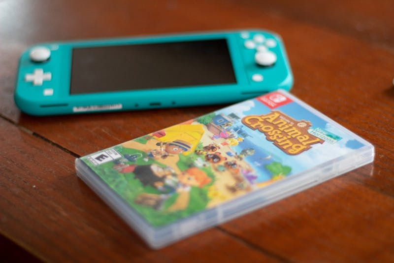 DTH Photo Illustration. A copy of Nintendo's Animal Crossing sits on a table with a Nintendo Switch Lite. Animal Crossing: New Horizons, the latest installment in the game franchise, was released on Friday, March 20, 2020.
