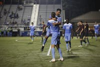 Senior Forward Nils Bruening (14) celebrates his goal with Sophomore Midfielder Raul Aguilera (28) during Saturday's game against Virginia Tech at Koskinen Stadium. UNC won 2-1.