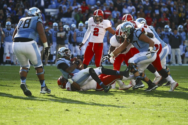 Junior quarterback Marquise Williams (12) is sacked by N.C. State defensive tackle T.Y. McGill (75). The Tar Heels lost 35-7 to the Wolfpack on Saturday.