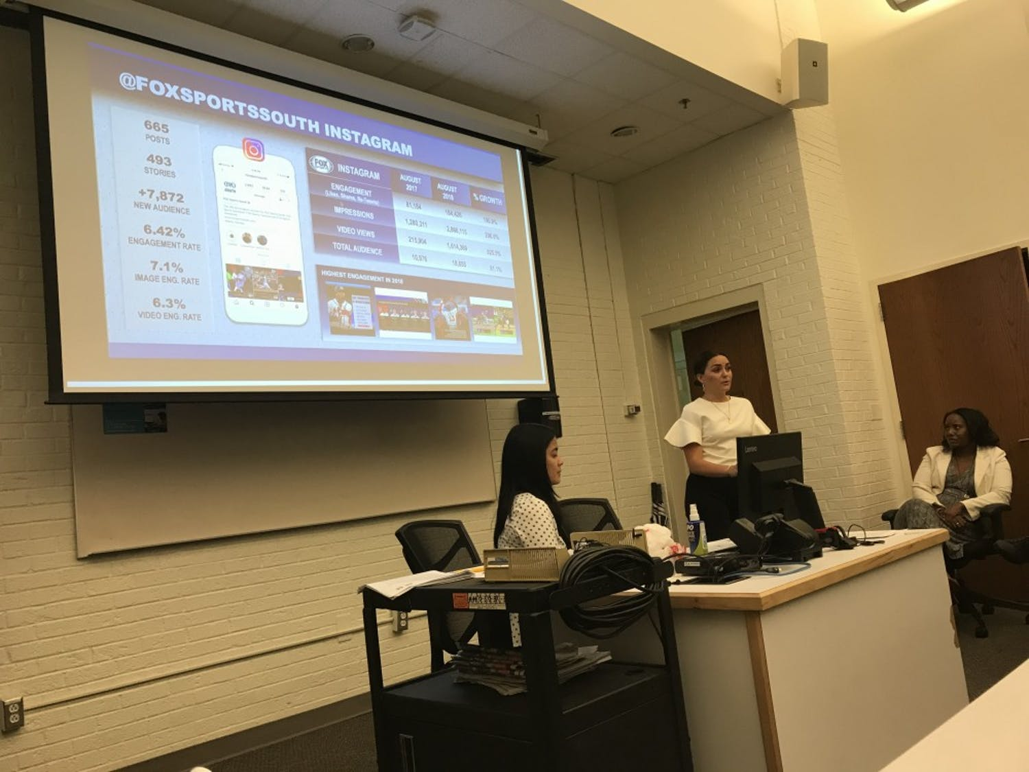 Fox personnel Micaela Asercion and Caroline Youngs speak in front of MEJO 634 on Sept. 27 in Carroll Hall.
