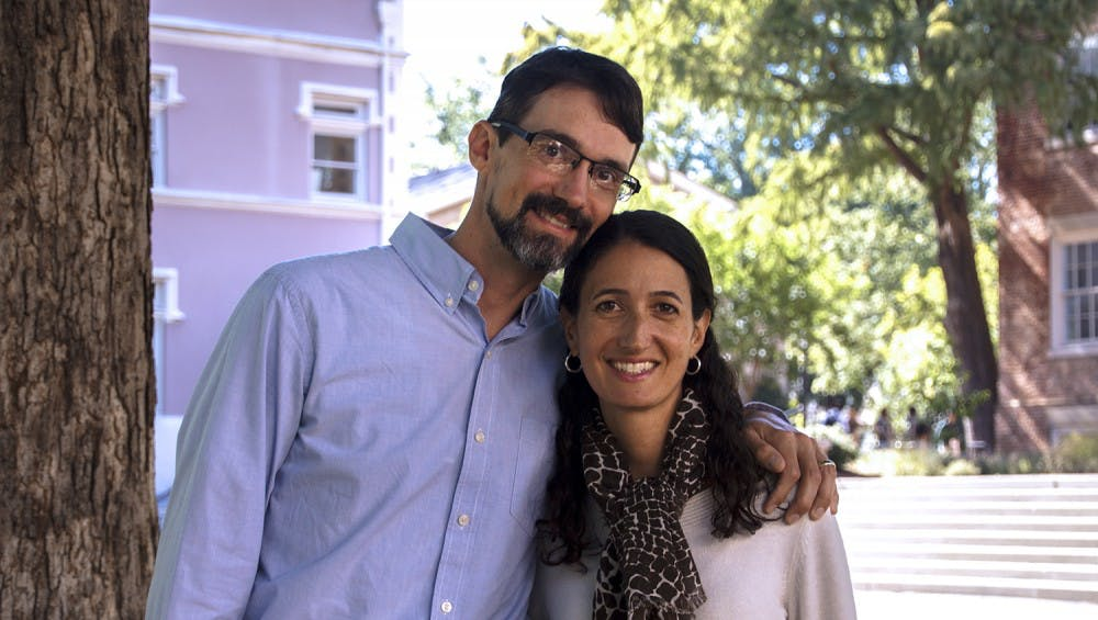 <p>Brian Hogan, a chemistry professor, and Kelly Hogan, a biology professor, pose next to the Old Well. The Hogan's made a video for the 2015 UNC teaching awards.</p>